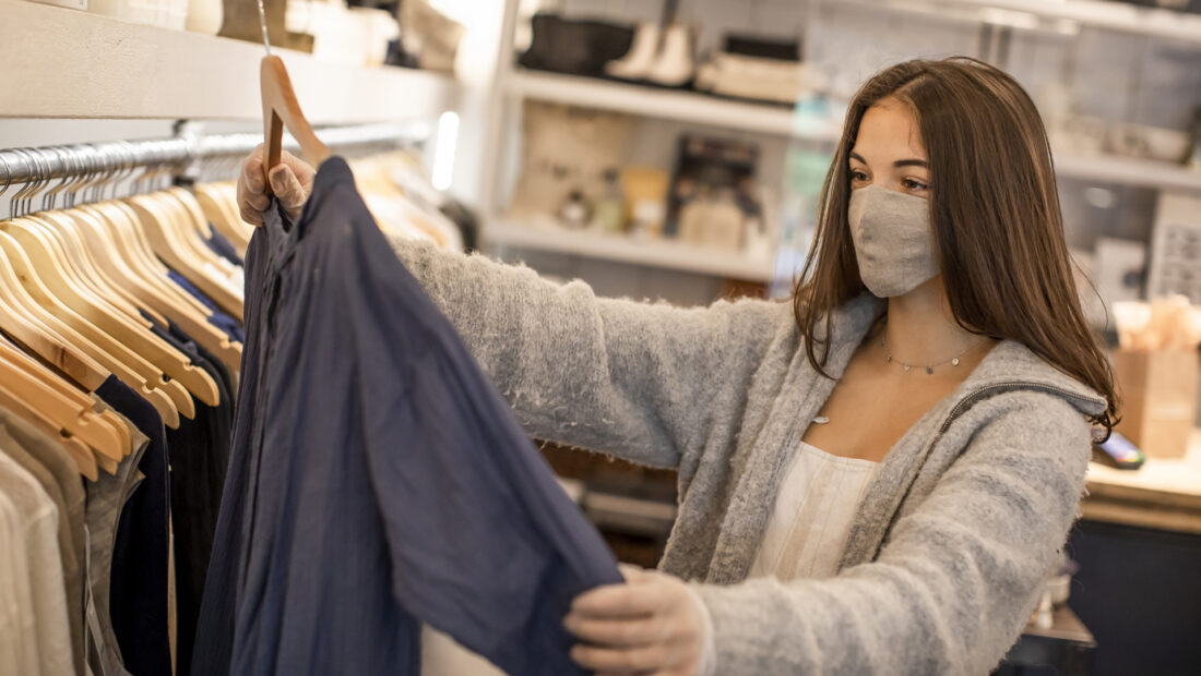 Young teenager shopping for clothing wearing protective gloves.