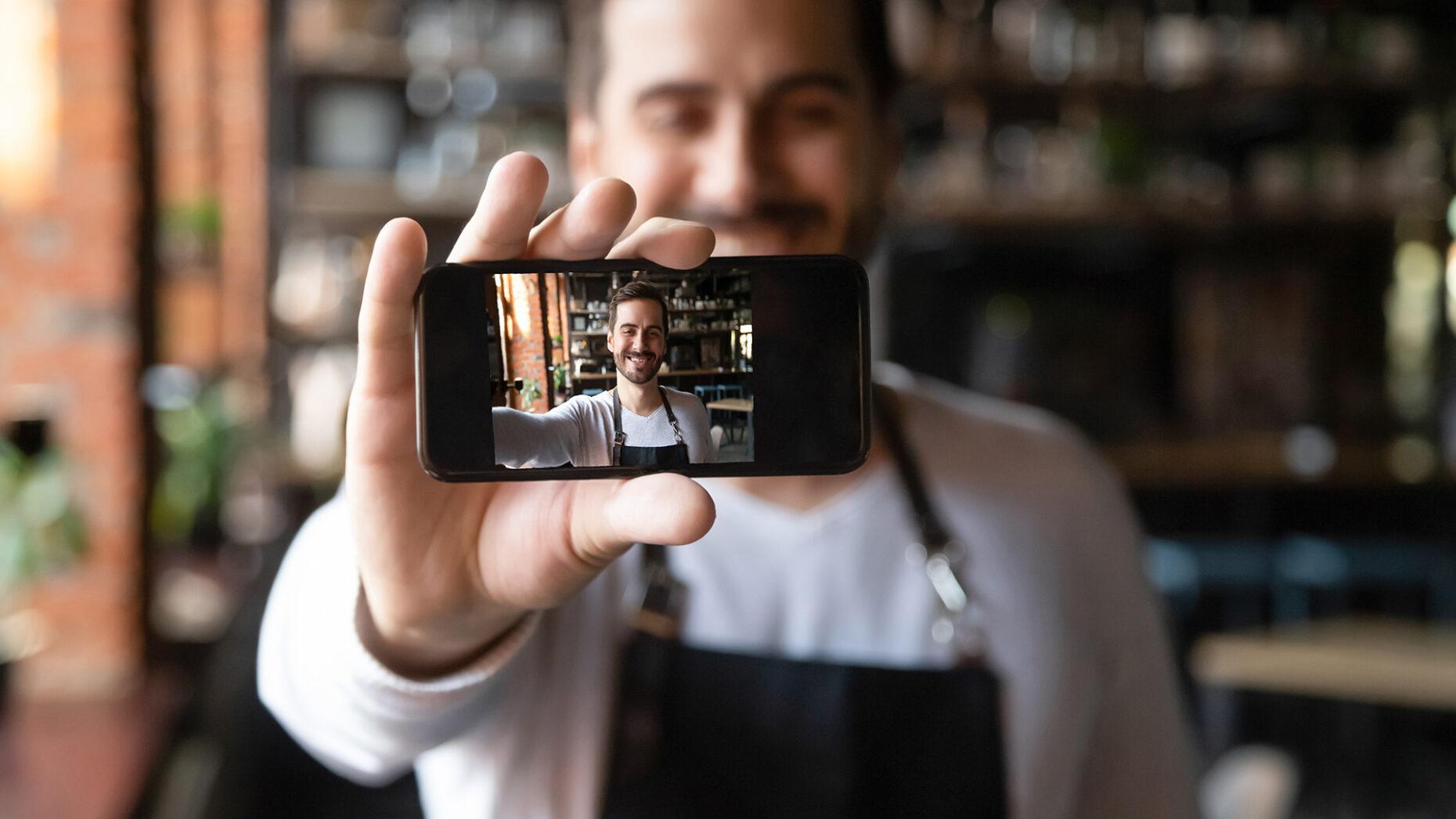 Smiling restaurant owner holding smartphone with camera on make selfie